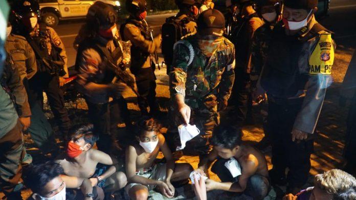 Anggota gabungan saat mengamankan sejumlah pemuda yang kedapatan menggelar pesta miras dan balapan liar Sabtu (6/6).