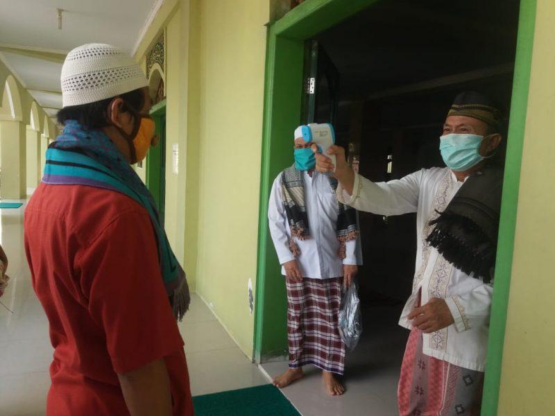 Pengurus masjid Agung saat memeriksa suhu tubuh jamaah salat Jumat, Jumat (12/6).