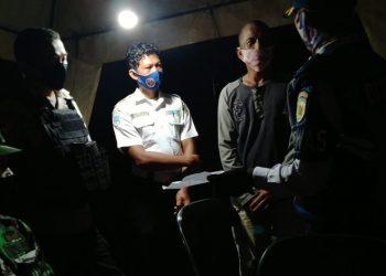 Petugas lintas batas Pos Sebangau di Kalampangan memeriksa sopir yang diduga menggunakan surat keterangan rapid test palsu, Kamis (16/7/2020) dinihari. Foto : Am