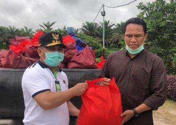 Penyerahan secara simbolis bantuan 300 sembako untuk korban banjir oleh Gubernur Kalteng H. Sugianto Sabran kepada Bupati Kabupaten Lamandau Hendra Lesmana. Foto : Ist