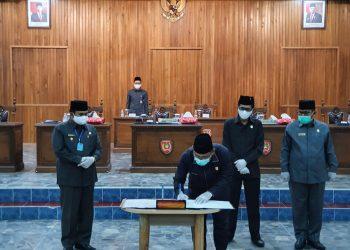 Ketua DPRD Kobar Rusdi Gozali saat menandatangai ranperda pertanggungjawaban APBD 2019 yang telah disepakati 6 fraksi untuk disahkan, Jumat (17/7).