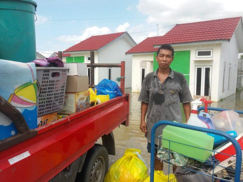 Korban banjir saat mengevakuasi perabotan rumah tangganya, Sabtu (25/7).