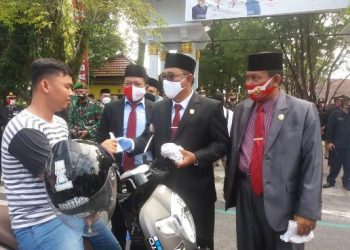 Ketua DPRD Kobar M Rusdi Gozali bersama Wakil Ketua II Bambang Suherman dan Direktur RSUD Fachrudin saat membagikan masker kepada pengendara Selasa (18/8).