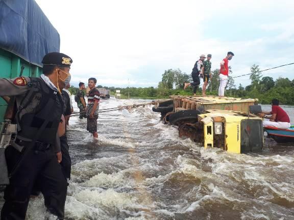 Anggota Polsek Kolam dan warga saat berupaya mengeakuasi truk yang terguling Senin (21/9).