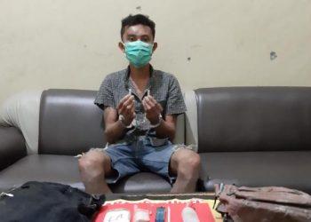 Tersangka saat diamankan  bersama barang bukti di Polres Gunung Mas Rabu (24/9).