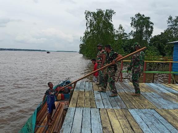 Anggota TMMD saat mengevakuasi material kayu dari kelotok ke daratan, Minggu (27/9).