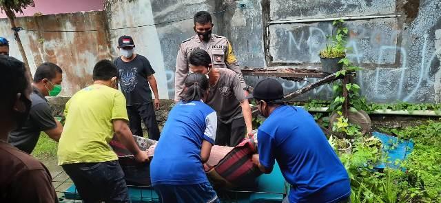 Anggota kepolisian bersama warga saat mengevakuasi jasad korban Minggu (27/9).