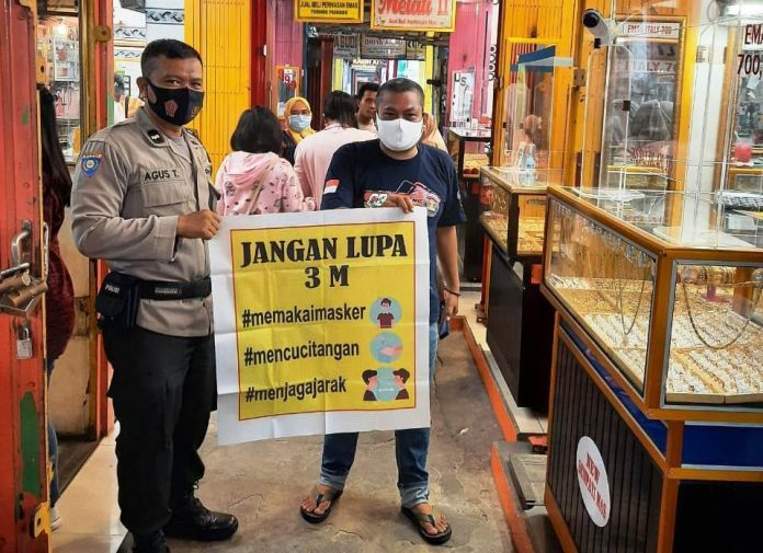 Bhabinkamtibmas Polsek Pahandut, Aipda Agus Triyanto saat menyambangi warga di Pasar Besar Kota Palangka Raya, Jumat (23/10/2020) siang. Foto : Tbn