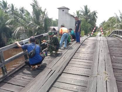 Anggota TMMD saat mengecat jembatan Handil Gayam.