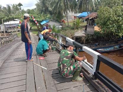 Personel TNI dan masyarakat bergotong-royong mengecat jembatan Sei Babirah.