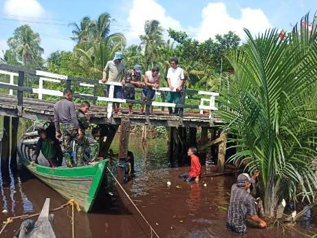 Anggota TNI saat gotong royong bersama warga memasang tiang jembatan Sabtu (3/10).