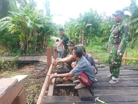 Anggota TNI bersama warga saat bergotong royong memperbaiki jembatan.