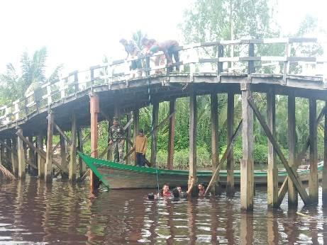 Anggota TNI dan masyarakat saat gotong royong memasang tiang jembatan Desa Babirah Minggu (4/10).
