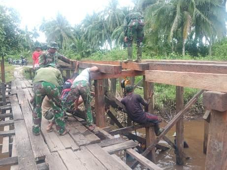 Anggota TNI ketika mengerjakan pembangunan jembatan dengan penuh semangat.