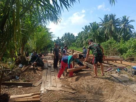 Anggota TNI dan warga terus semangat gotong royong membangun jembatan.