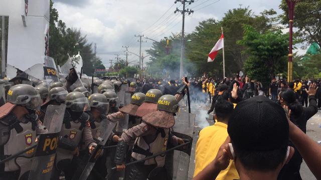Petugas Dalmas dari kepolisian saat menghalau massa yang hendak masuk ke dalam gedung DPRD Kalteng Kamis (8/10).
