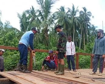 Anggota TNI bersama warga saat memasang lantai jembatan Minggu (11/10).