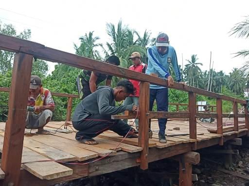 Anggota TNI bersama warga saat mengerjakan pembangunan jembatan.