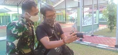Anggota TNI saat mengamati dokumentasi di kamera.