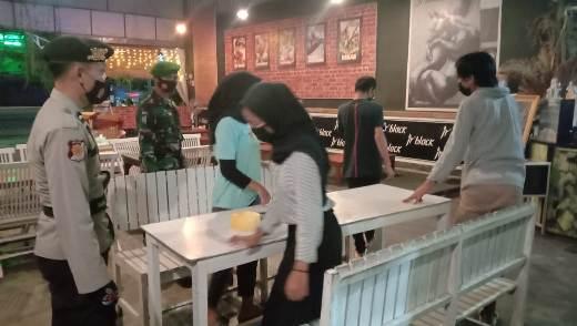 Anggota saat membubarkan muda-mudi yang sedang nongkrong di kafe hingga larut malam, Selasa (12/1).