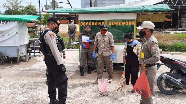 Salah seorang warga saat terjaring dan disanksi menyapu sampah Minggu (24/1).