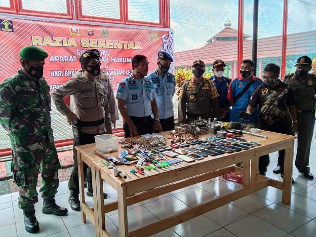 Petugas gabungan saat memperlihatkan hasil giat razia di Lapas Narkotika, Rabu (7/4).