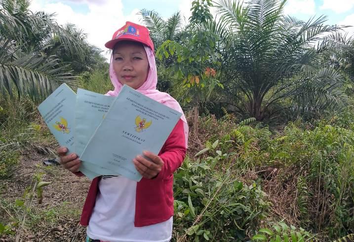 Salah seorang warga saat memperlihatkan sertifikat tanah di lokasi tanah yang disengketakan dengan PT. KSS, Senin (5/7).