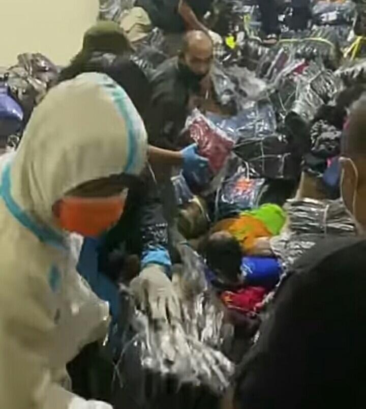 Petugas dan warga saat mengevakuasi jasad ketiga korban yang tertimbun tumpukan pakaian, Jumat (10/9) malam.