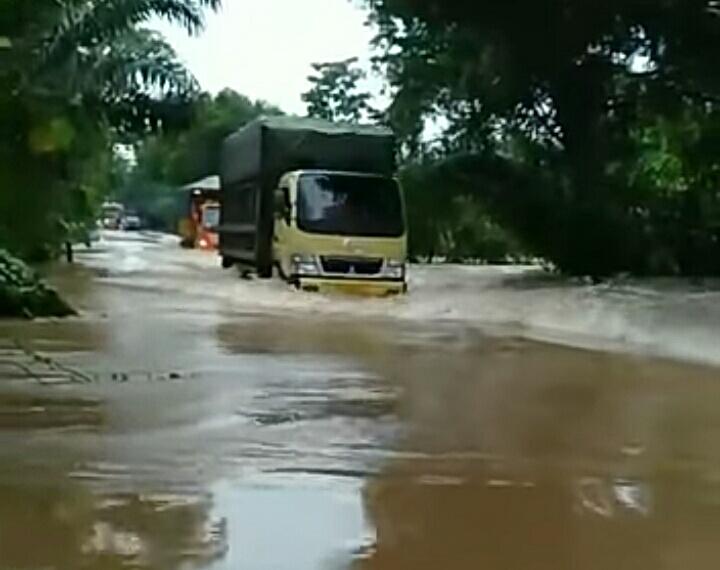 Sebuah kendaraan truk saat melintasi ruas jalan yang direndam banjir, Rabu (5/9).