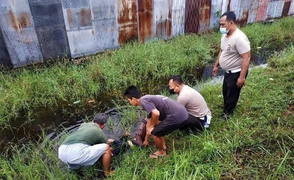 Anggota kepolisian saat mengevakuasi jasad korban di parit, Rabu (15/9).